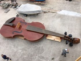 40-foot-violin-boat,-noah's-violin,-launches-with-cellist-playing-on-the-deck