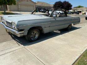 here's-a-1964-chevrolet-impala-sitting-on-the-side-of-the-road-with-huge-holes-in-it