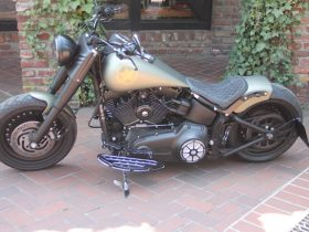 harley-davidson-fat-boy-ready-for-the-army,-rides-on-black-solid-design-wheels