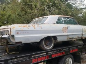 this-1964-chevrolet-impala-ss-sleeps-tight-on-a-trailer,-likely-forgotten-for-many-years